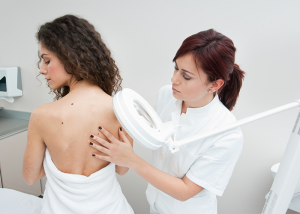 Woman getting her back moles examined by a doctor.