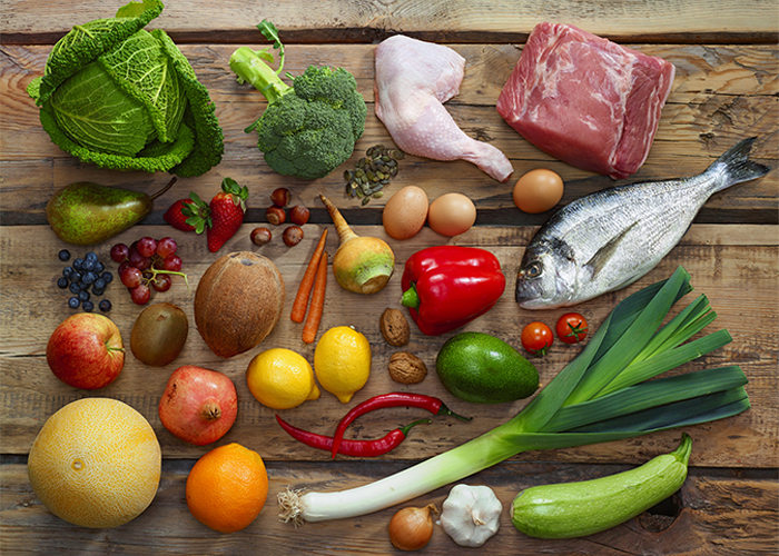 Flat lay of pegan (paleo-vegan) diet foods such as vegetables, fruits, fish, lean eat proteins