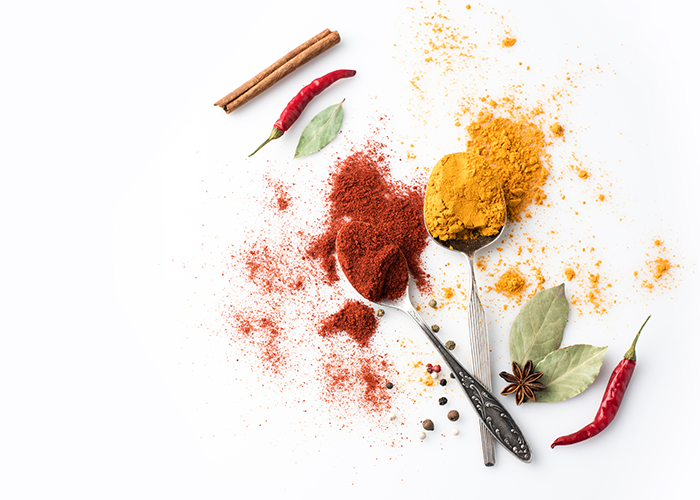 Top down view of spice powders on tablespoons, and fresh spices laid out on a white surface