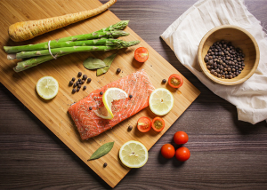 Top down view of pegan 365 diet (paleo-vegan) foods such as salmon, asparagus, carrot, lemons, and tomatoes on a wooden board being prepped for cooking
