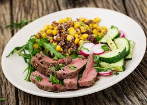 White plate topped with a corn, cucumber and radish salad and a small portion of lean red meat