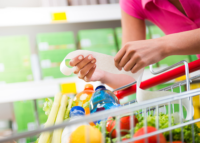 Woman with a shopping cart filled with groceries looking at her shopping bill