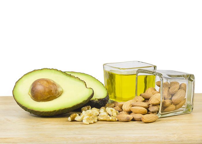 Two halved avocados, nuts, and olive oil in a small square glass bowl on a wooden table