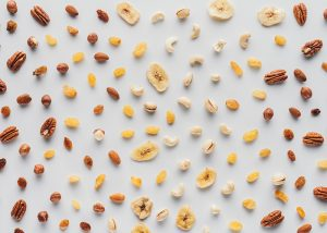 Flat lay of dried fruits and nuts laid out neatly on a white table