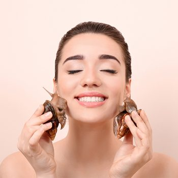 young woman holding two snails to her face for snail mucin