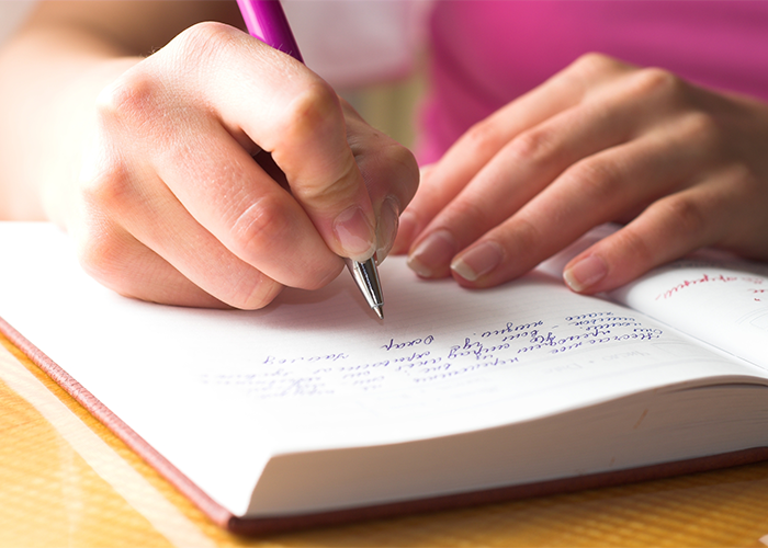 Close up of woman journaling and writing in her journal