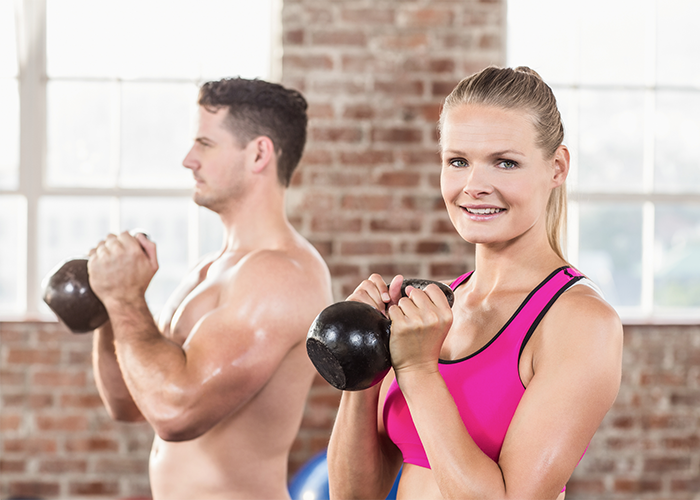 Woman smiling and holding a kettlebell ready for a goblet squat
