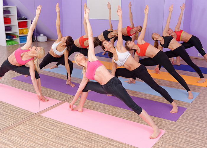 Group of women doing a hot yoga class in a studio