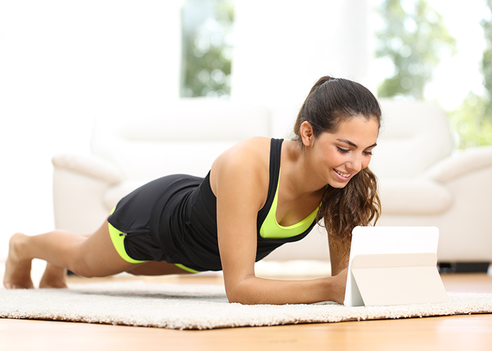 Fit woman doing planks at home following instructions from workout app for women