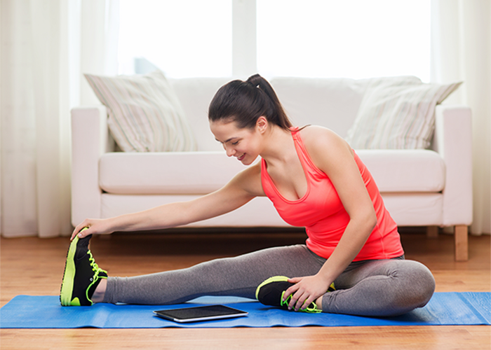 Woman doing stretching at home on a yoga mat with instructions from workout app for women