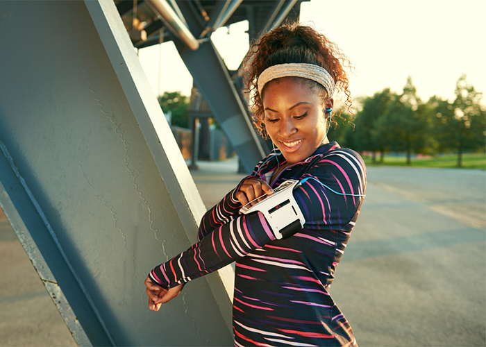 African American woman outdoors setting her workout app for women before a run