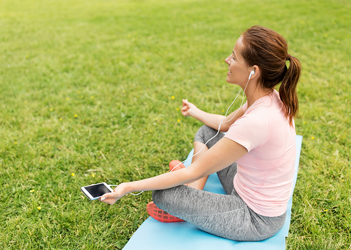 woman doing yoga outdoors with yoga app