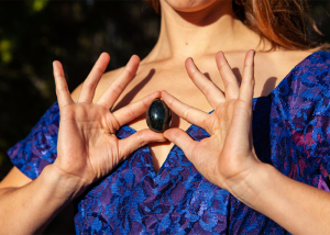 Woman holding a black yoni egg up to her chest
