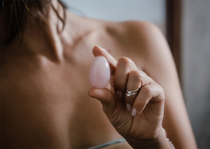 Woman holding a pink yoni egg with her finger and thumb