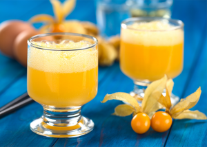 Two glasses of golden berry smoothie with a couple of golden berries next to it on a blue table.
