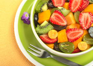 Golden berries on top of a colorful bowl of fruit salad with kiwi, strawberries, melons, and grapes.