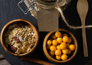 Top down view of a bowl of oats next to a bowl of golden berries and wooden spoon, with partial view of a jar.