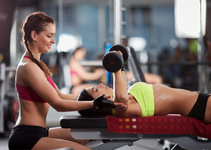 Female trainer helping young woman with chest and triceps workout