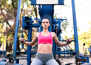 Woman doing chest and tricep workout outdoors with a machine