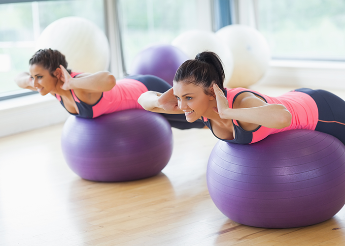 Woman using exercise balls for lower back workouts.