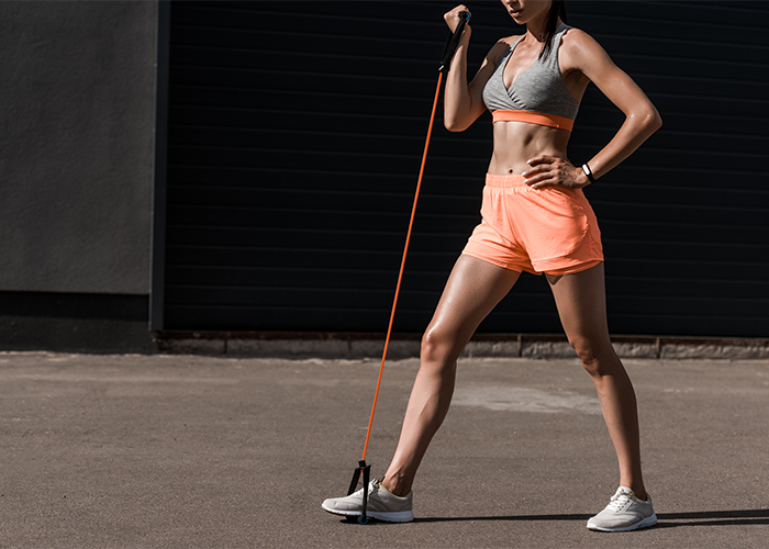 Woman doing a resistance band press outdoors
