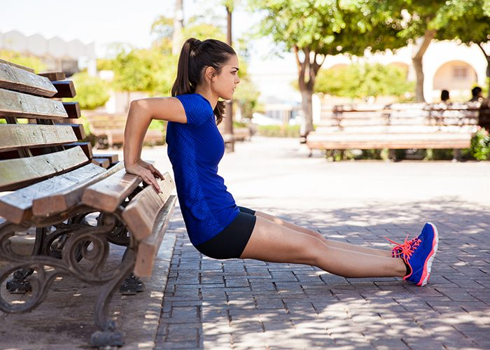 Young woman doing tricep dips outdoors to workout chest and triceps