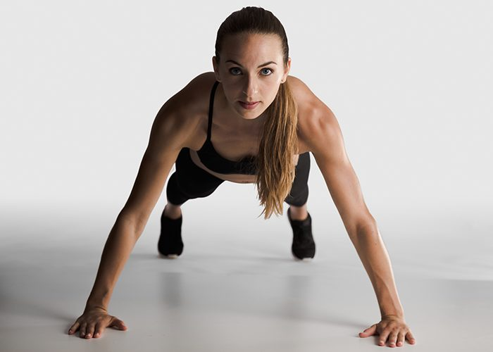 Woman doing wide arm pushups as part of her chest and tricep workout