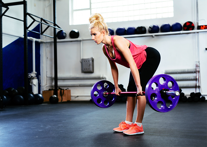 Blonde woman doing straight leg dead lifts for lower back workout.
