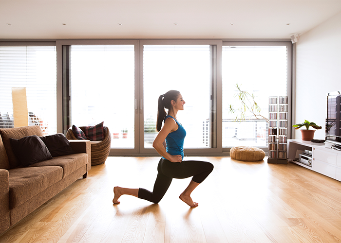 Woman doing lunges in her living room for a calisthenics workout