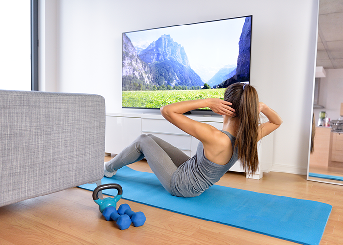 Woman doing crunches at home while watching TV.