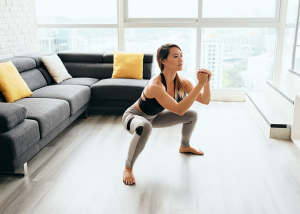 Woman doing squats in a well-lit living room for a calisthenics workout