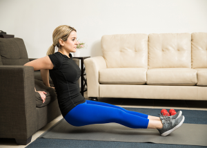 Women doing chair dips using her couch as part of a calisthenics workout.
