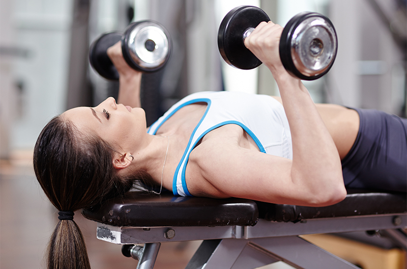 woman using dumbells in chest and tricep workout