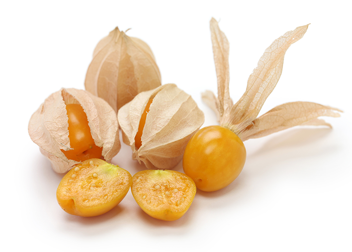 Close up of some golden berries in husks, an open berry, and a halved golden berry on a white surface.
