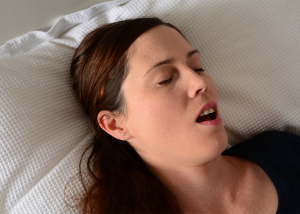 Woman snoring in bed with her mouth open.