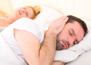 Couple in bed with woman snoring and man covering his ears.