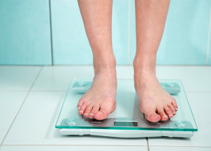 Close up of woman's legs standing on a weight scale in the bathroom.