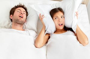 couple in bed with man snoring and woman looking annoyed and covering her ears with her pillow