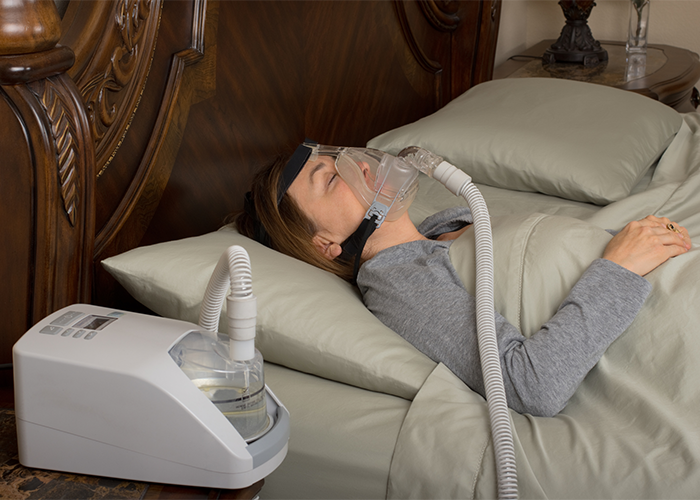 Woman in bed wearing a CPAP as she sleeps in bed.