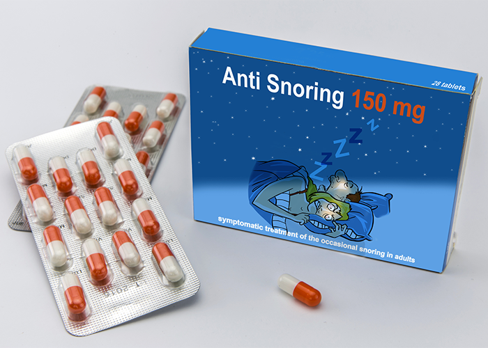 A blue box of anti snoring tablets with pill packets next to it.