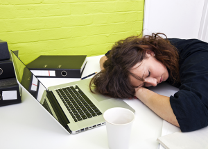 Woman asleep at her office desk.