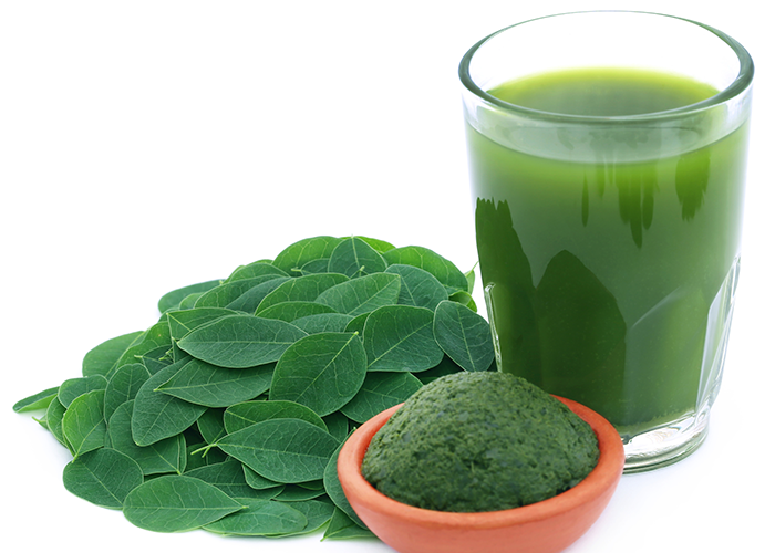 Moringa tea in a glass beside moringa leaves and paste