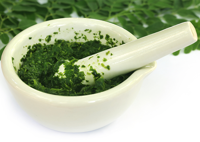 Moringa leaves ground up in a mortar with a pestle on top