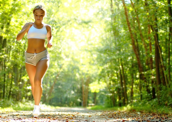 Blonde woman running for weight loss on a forest trail