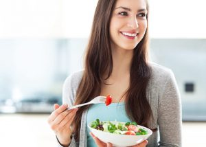 Young woman holding and eating a bowl of salad in the kitchen