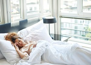 Woman sleeping in bed with lots of natural light from her windows