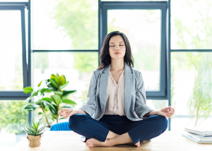 Woman sitting on her office desk doing meditation for stress relief