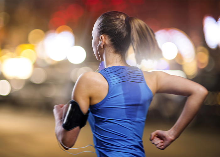 Back view of a woman running for weight loss outdoors in the evening with defocused lights in front of her