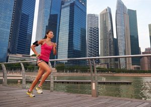 Woman running for weight loss outdoors with a city landscape