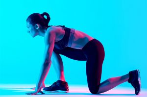 woman in a running starter position with a neon blue background